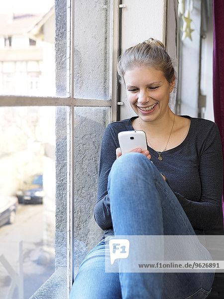 Lächelnde junge Frau mit ihrem Smartphone
