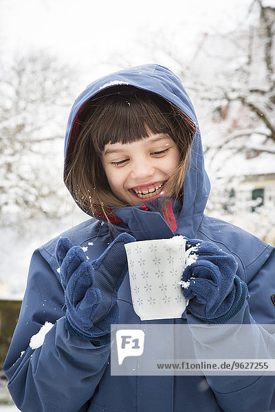 Portrait of smiling girl with cup of tea in winter