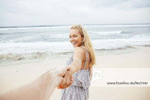 Indonesien  Bali  lächelnde Frau am Strand zieht Hand eines Mannes