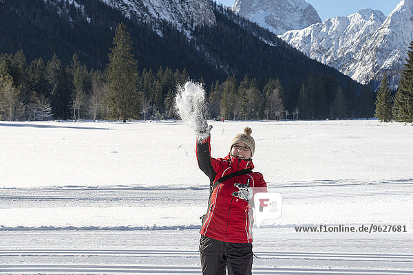 Austria  Tyrol  Pertisau  young woman throwing snowball