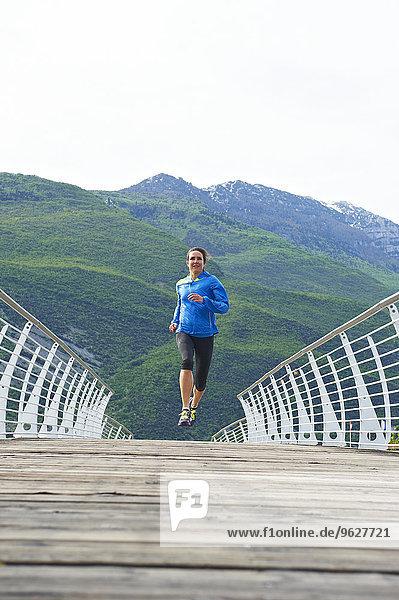 Italien  Trentino  Frau läuft auf Fußgängerbrücke am Gardasee