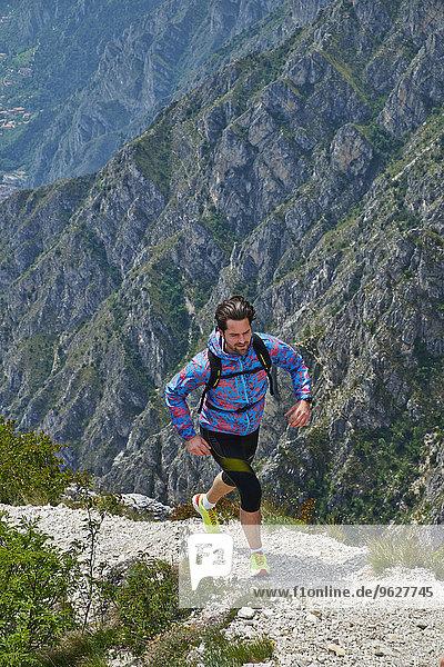 Italy  Trentino  man mountain running near Lake Garda
