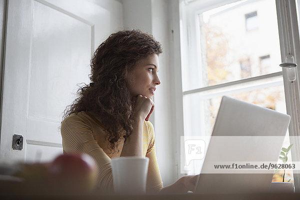 Junge Frau zu Hause mit Laptop