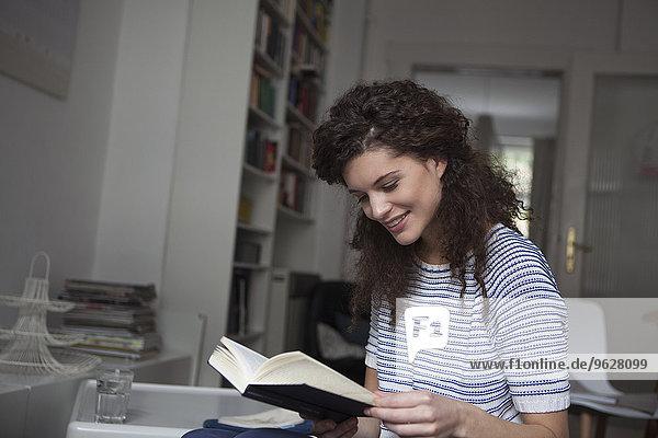 Junge Frau zu Hause liest Buch