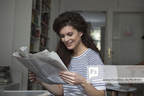 Junge Frau zu Hause beim Zeitungslesen