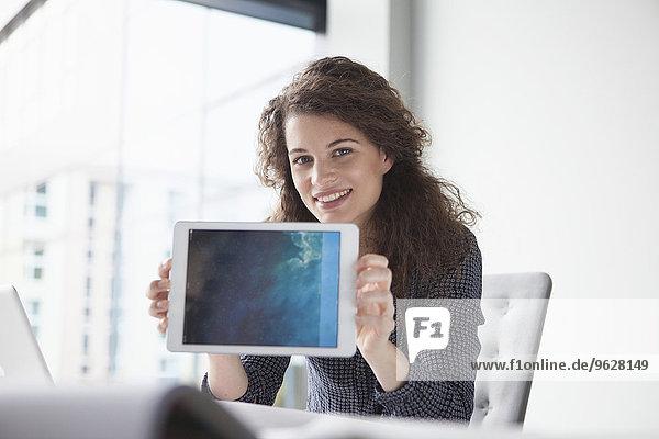 Porträt einer lächelnden jungen Frau am Schreibtisch mit digitalem Tablett