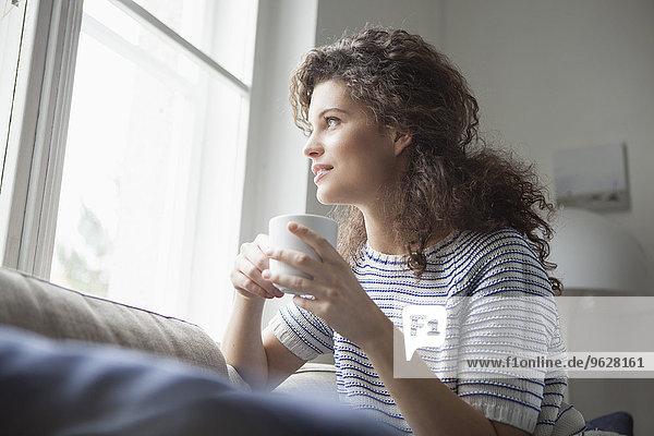 Lächelnde junge Frau mit einer Tasse Kaffee aus dem Fenster schauend