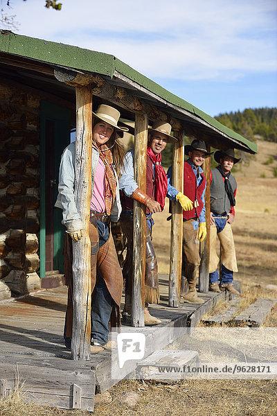 USA  Wyoming  Cowgirl und drei Cowboys stehen unter einer Veranda.