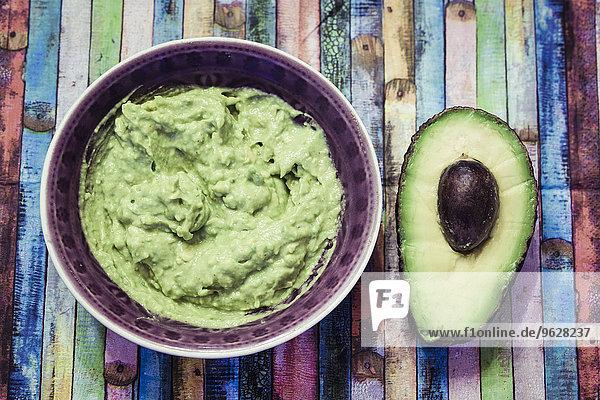 Schale mit Guacamole und geschnittener Avocado