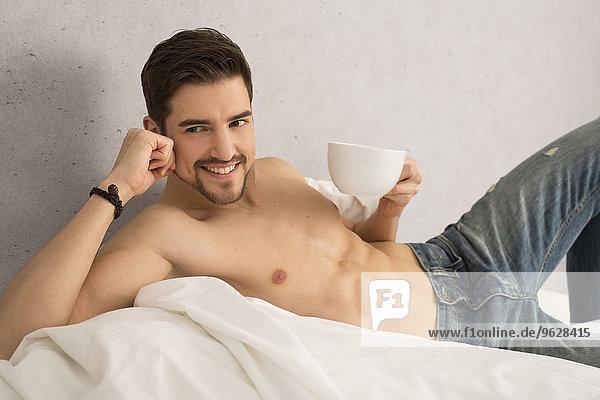 Mann ohne Hemd mit Tasse Kaffee auf dem Bett liegend