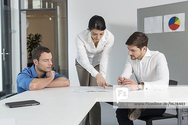 Treffen von drei Geschäftsleuten in einem Konferenzraum