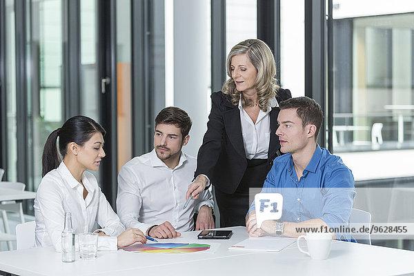 Treffen von vier Geschäftsleuten in einem Konferenzraum
