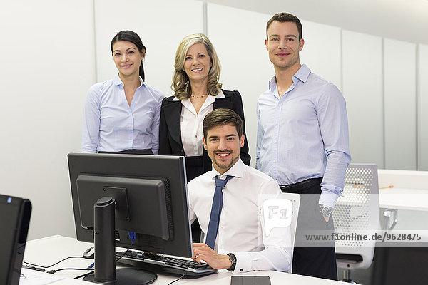 Porträt von lächelnden Geschäftsleuten am Schreibtisch im Büro