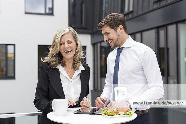 Lachender Geschäftsmann und Geschäftsfrau bei der Mittagspause