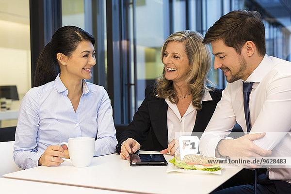 Geschäftsleute bei der Mittagspause mit digitalem Tablett in der Kantine