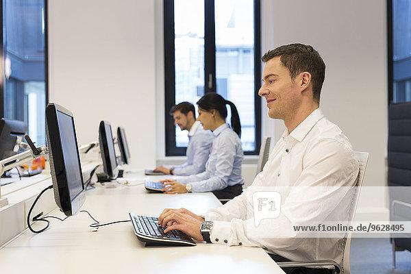 Mann am Schreibtisch mit Computer und Kollegen im Hintergrund