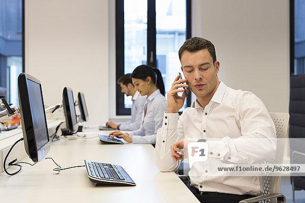 Mann am Schreibtisch am Handy mit Kollegen im Hintergrund