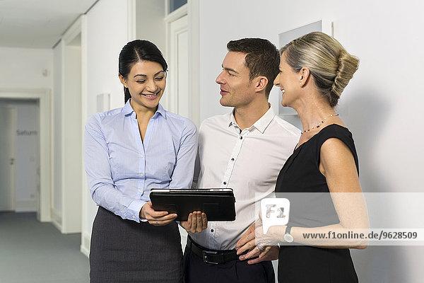 Geschäftsleute mit digitalem Tablett im Bürogeschoss