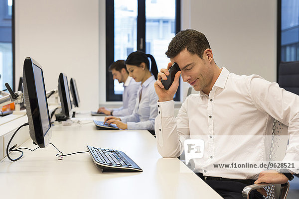 Frustrierter Mann am Schreibtisch mit Kollegen im Hintergrund