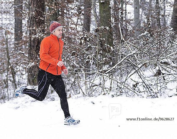 Deutschland  Baden-Württemberg  Holzberg  Mann joggen im Schnee