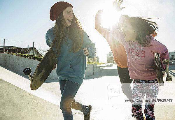 Drei Mädchen laufen im Skatepark