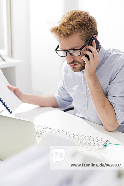 Junger Geschäftsmann am Schreibtisch am Handy