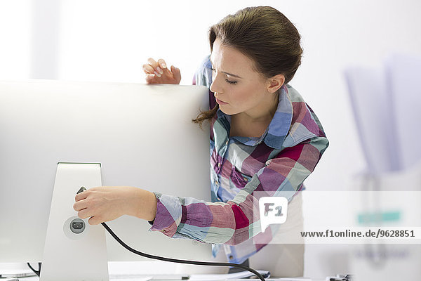Young woman in office connecting computer screen