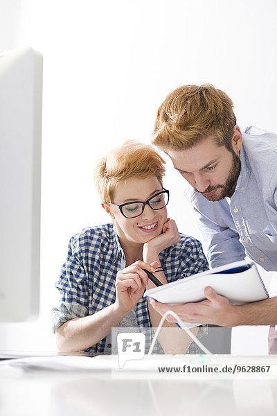 Junge Frau und Mann mit Notizblock am Schreibtisch