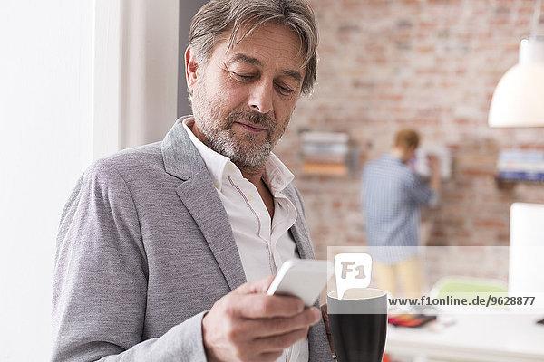 Geschäftsmann mit Handy und Tasse Kaffee im Büro