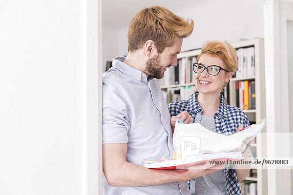 Lächelnde junge Frau und Mann diskutieren Dokument