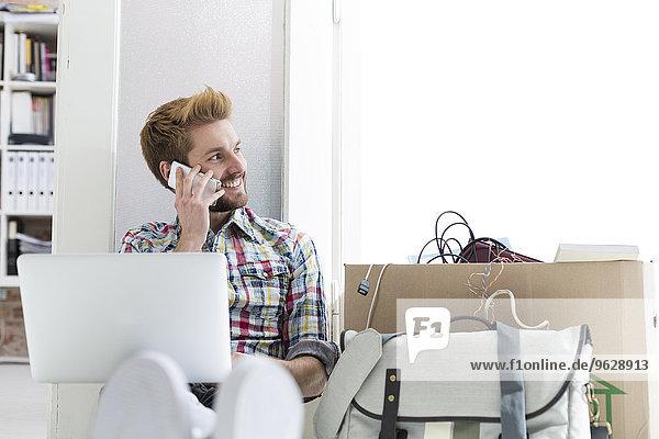 Junger Mann im Büro auf dem Boden sitzend mit Laptop und Handy