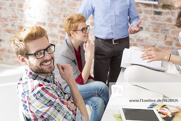 Lächelnder junger Mann beim kreativen Geschäftstreffen im Sitzungssaal