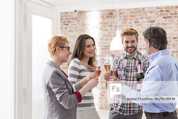 Fröhliche Geschäftsleute stoßen mit Champagnergläsern an.