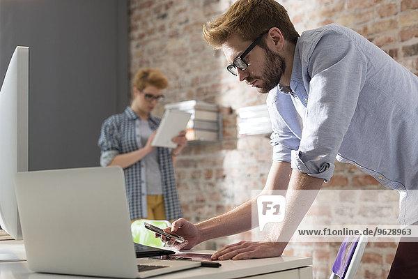 Junger Mann am Schreibtisch mit Handy und Laptop