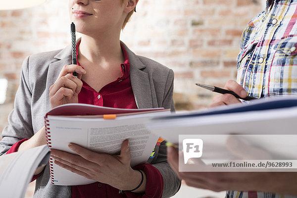 Geschäftsmann und Geschäftsfrau beim Notieren im Amt