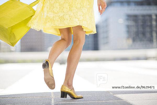 Gelb gekleidete Frau mit goldenen Schuhen und Einkaufstasche
