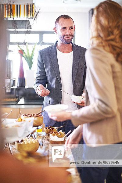 Geschäftsmann und Geschäftsfrau beim Frühstücksbuffet