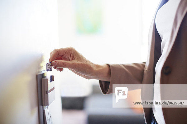 Frau mit elektronischer Keycard an der Hotelzimmertür