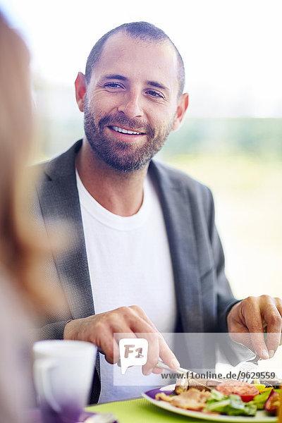 Lächelnder Geschäftsmann beim Mittagessen