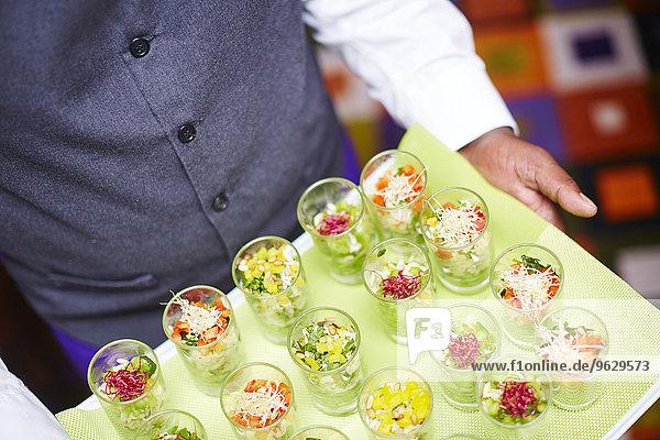 Kellnertablett mit einzelnen Salaten in Gläsern