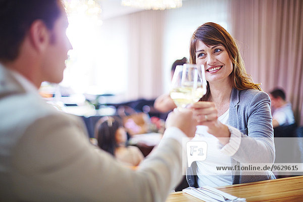 Business associates clinking wine glasses in hotel restaurant
