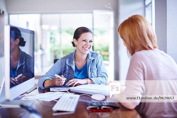 Zwei Frauen sitzen zu Hause am Schreibtisch und arbeiten.