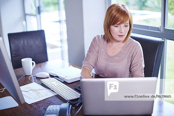 Frau am Schreibtisch bei der Arbeit mit dem Laptop