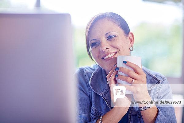 Lächelnde Frau hält eine Kaffeetasse und schaut auf den Computerbildschirm