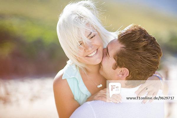 Junges Paar umarmt den Strand