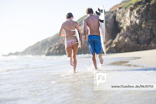 Junges Paar  das mit seinen Surfbrettern am Strand läuft