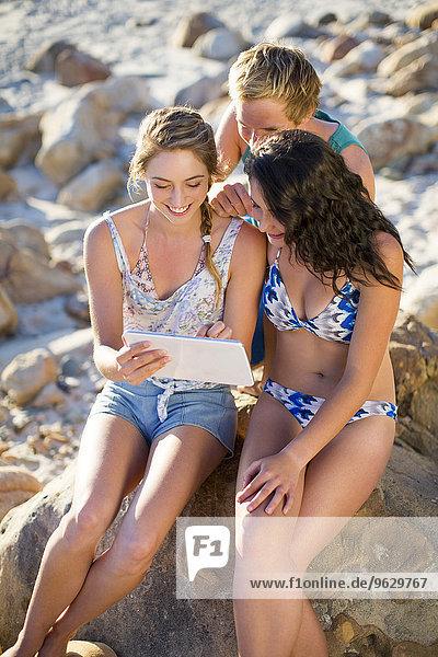 Freunde  die mit einer Tafel am Strand interagieren