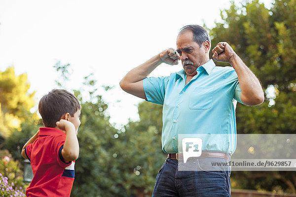 Großvater und Enkel biegende Arme im Garten