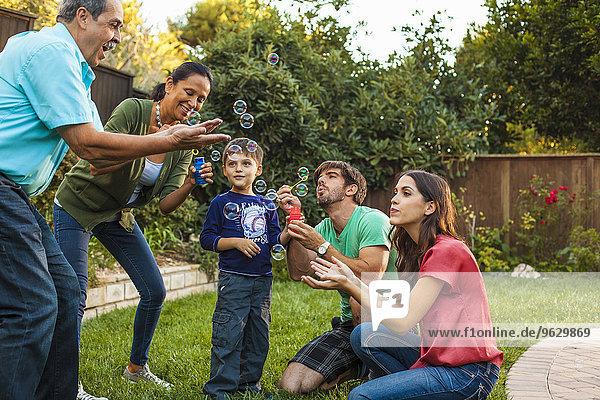 Drei Generationen Familie blasen Blasen im Garten