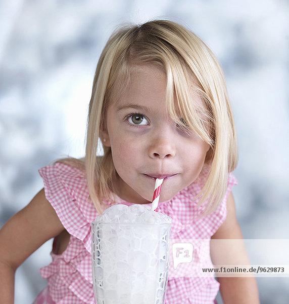 Porträt eines süßen weiblichen Kleinkindes  das Blasen in ein Glas Milch bläst. Porträt eines süßen weiblichen Kleinkindes, das Blasen in ein Glas Milch bläst.